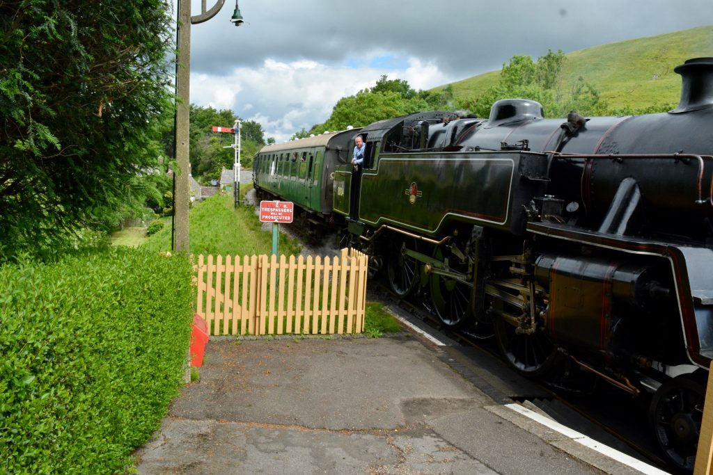 Steam train pulling in to Corfe Castle station